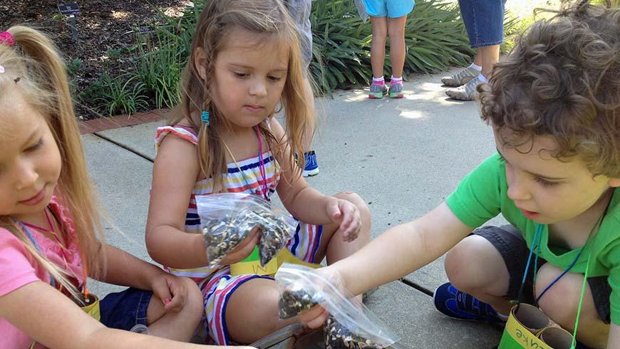 children filling bird feeder